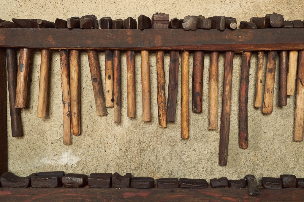 Wall rack of old hammers.