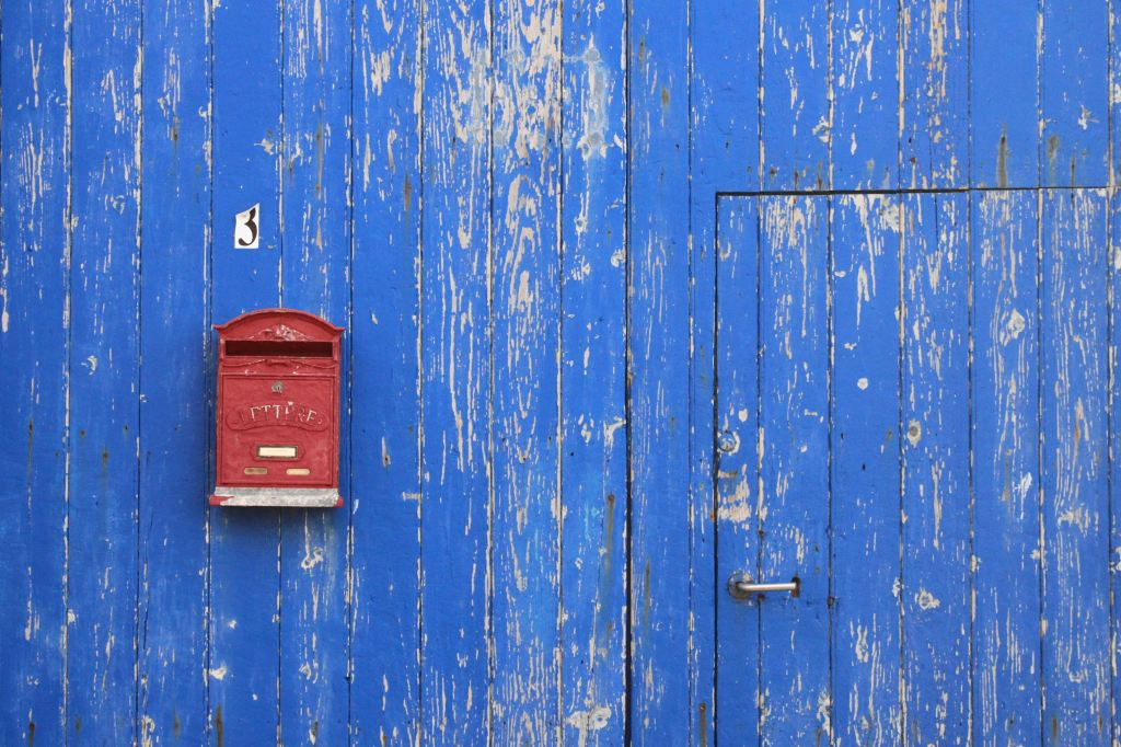 Mailbox on a blue wall.