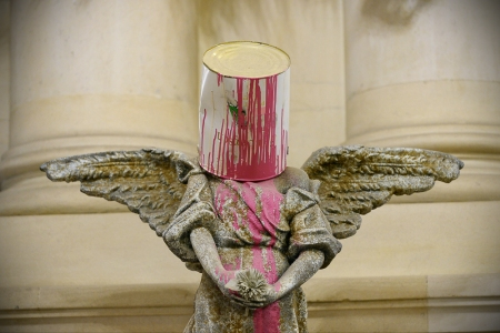 Angel sculpture with bucket of paint on its head