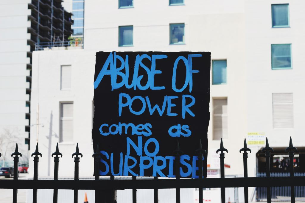 "Painted sign saying ""Abuse of power comes as no surprise."""