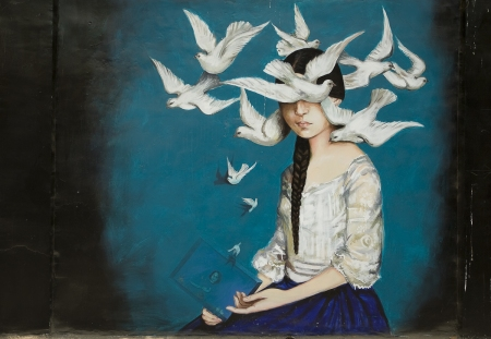 Graffiti of a girl surrounded by white doves