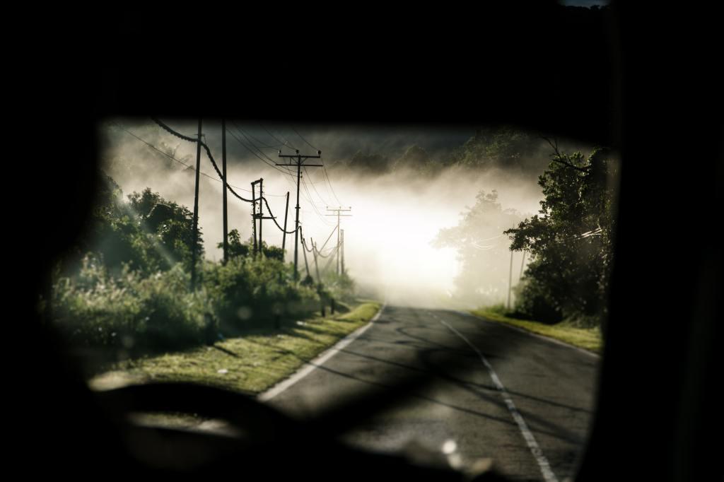 Road seen through a car's window onto a dark road.
