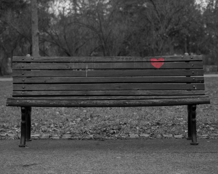 Park bench with a heart painting on the back.