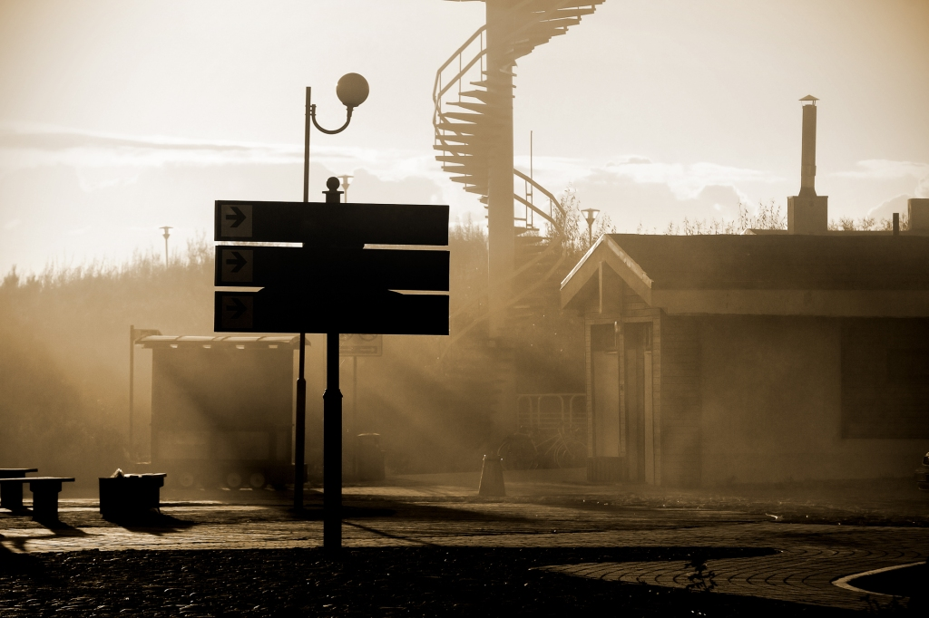 A train station platform in soft fading afternoon light.