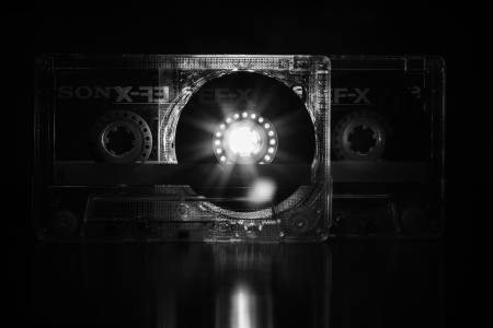 Cassette tape with light shining through it's clear body.